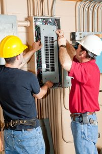 two electricians working with an electrical panel