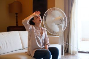woman-feeling-hot-and-cooling-off-in-front-of-fan