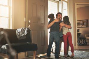 family-hugging-in-frong-of-home-door