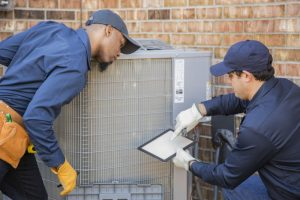 two-technicians-looking-over-outside-air-conditioner-unit-with-checklist
