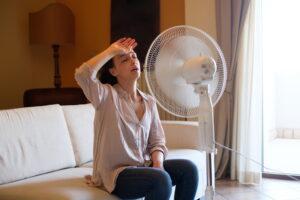 woman-looking-hot-sitting-in-front-of-fan