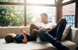 dad-and-son-sitting-in-front-of-large-windows