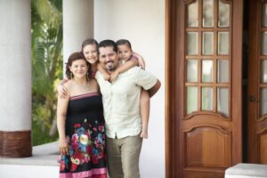 Family-posing-for-photo-in-front-of-beautiful-new-front-door