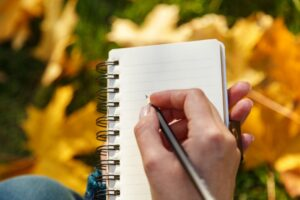 hand-writing-on-paper-with-fall-leaves-in-background