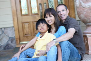family-sitting-in-front-of-home-with-pretty-front-door